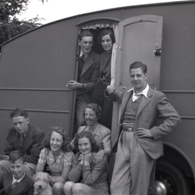M3XX34 1950s, historical picture showing a large British family group, men, women and children and pet dog, sitting outside and standing at the entrance to their holiday caravan parked in a field, England, UK.